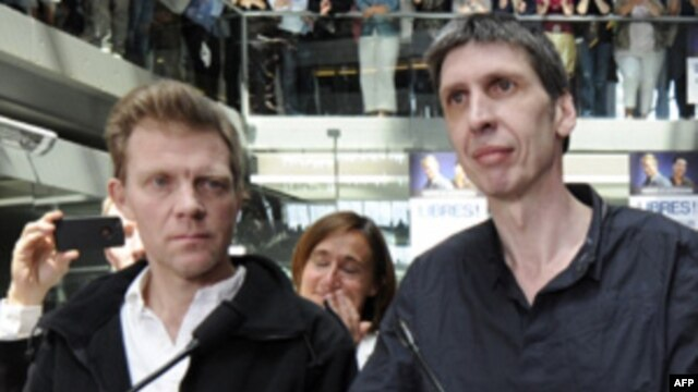 Nhà quay phim kiêm phóng viên Stephane Taponier (phải) và phóng viên Herve Ghesquiere (trái) của kênh truyền hình France-3 trở về Pháp sau khi được phóng thích