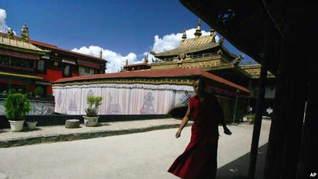 FILE - A Tibetan monk walks along the halls of the Jokhang Buddhist temple in Lhasa, Tibet.
