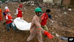 ကယ္ဆယ္ေရးလုပ္သားေတြက အေလာင္းေတြကို ရွာေဖြသယ္ေဆာင္လာစဥ္ (၇ ေမ ၂၀၁၃)