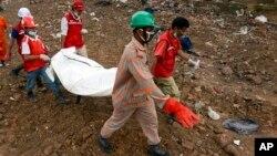 Regu penyelamat mengangkat jenazah korban dari reruntuhan gedung di Savar, Bangladesh (7/5).