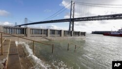 FILE - In this Jan. 11, 2017, photo, water from a king tide floods a staircase along the Embarcadero in San Francisco. California's Ocean Protection Council decided April 26, 2017, to update its sea-rise guidance for state and local governments.