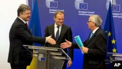 Ukrainian President Petro Poroshenko (L) is seen following a joint news conference with European Council President Donald Tusk (C) and European Commission President Jean-Claude Juncker at the EU Council building in Brussels, March 17, 2016.