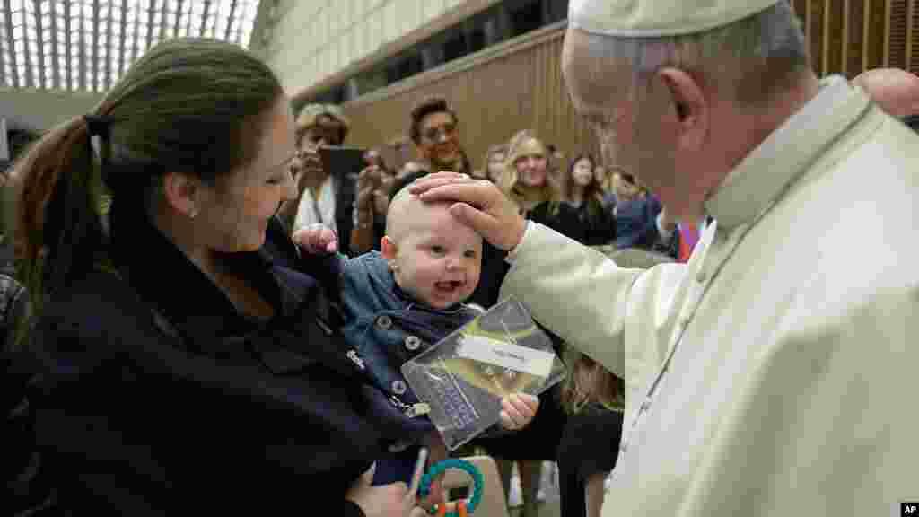 Le Pape François pose sa main sur un bébé à la fin du congrès sur les progrès de la médecine régénérative, 29 avril 2016.