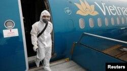 Một nhân viên Vietnam Airlines tẩy trùng máy bay.