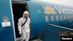 Nhân viên y tế phun thuốc khử trùng máy bay của Vietnam Airlines.