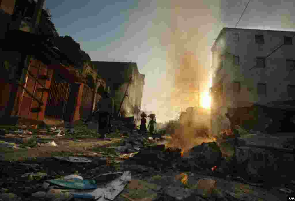 January 18: People walk through fire and rubble in the market area in Port-au-Prince, Haiti. (AP Photo/Gerald Herbert)