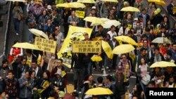 ພວກປະທ້ວງທີ່ຖືຄັນຮົ່ມສີເຫຼືອງ ຊຶ່ງເປັນສັນຍາລັກ ຂອງຂະບວນການ ເຂົ້າຍຶດຄອງ ຫລື Occupy ພາກັນເດີນຂະບວນ ຢູ່ຖະໜົນໃນຮົງກົງ, ວັນທີ 1 ກຸມພາ 2015.