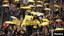 Para demonstran membawa payung kuning, simbol gerakan Occupy, berbaris di jalanan di Hong Kong (1/2). (Reuters/Liau Chung-ren)