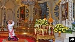 와치라롱꼰 태국 신임 국왕이 1일 즉위식에서 선왕인 푸미폰 국왕 부부 초상화에 존경을 표하고 있다.