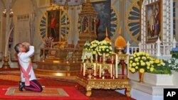 In this photo released by Bureau of the Royal Household, Thailand 's new king Maha Vajiralongkorn Bodindradebayavarangkun pays his respects to a portrait of the late Thai King Bhumibol Adulyadej and Thai Queen Sirikit at the Dusit Palace Dec.1, 2016.