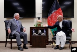 FILE - Secretary of State Rex Tillerson, left, speaks with Afghan President Ashraf Ghani before their meeting, Oct. 23, 2017, at Bagram Air Field, Afghanistan.