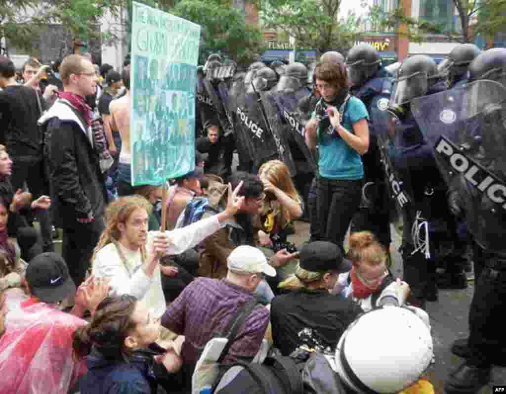 В центре с плакатом – житель Торонто Адам Чакрофт. Он сторонник того, чтобы демонстрации были мирными