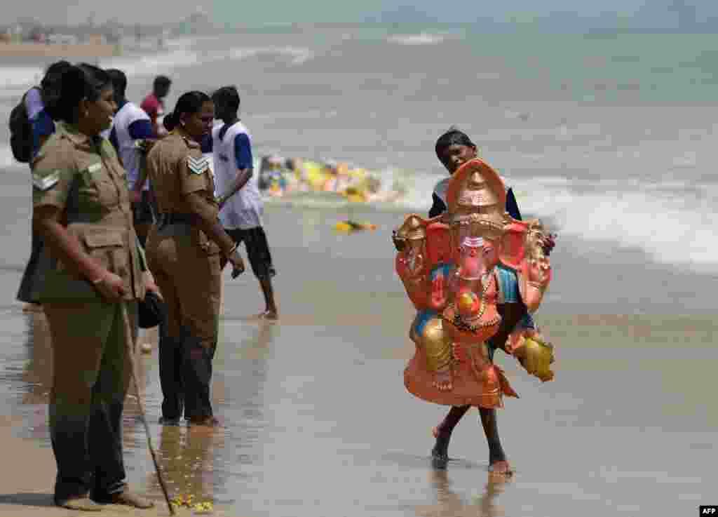 ក្មេងម្នាក់លើករូបសំណាកព្រះគនេសសម្រាប់ការជ្រមុជទឹកនៅមហាសមុទ្រឥណ្ឌា នៅឆ្នេរ Pattinapakkam ក្នុងក្រុង Chennai ប្រទេសឥណ្ឌា ដែលជាផ្នែកមួយនៃពិធីបុណ្យ Ganesh Chaturthi។