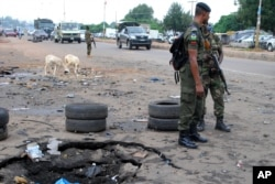 FILE - Police officers stand next to a checkpoint near the site of a blast in Kaduna, Nigeria, July 24, 2014.