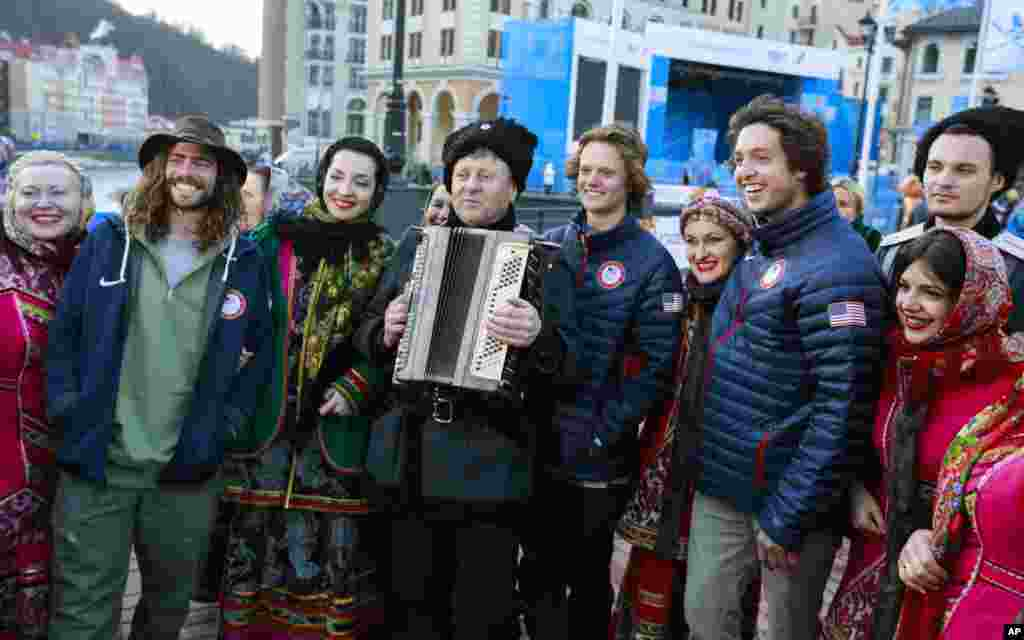 Members of the U.S. freestyle skiing team pose with members of a Cossack dancing chorus dressed in traditional costumes in Rosa Khutor, Feb. 6, 2014.