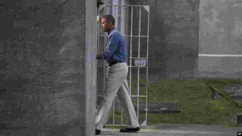 President Obama walks into a cell block during a tour of Robben Island.