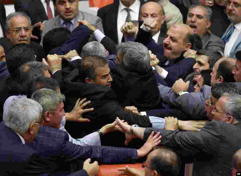 Legislators from Turkish Prime Minister Recep Tayyip Erdogan's party and the opposition Nationalist Action Party brawl at the parliament in Ankara, during a debate on whether parliament should open an inquiry into Islamic militants joining the fighting in Iraq and Syria, using Turkey's territory.