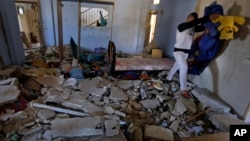 Personal belongings are removed from inside the home of Hamza Abu el-Heija, where he was killed by Israeli troops, in the West Bank refugee camp of Jenin, Mar. 22, 2014.