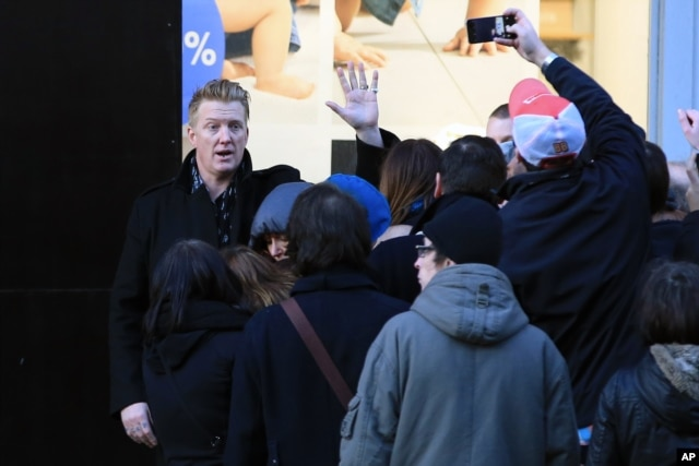 Josh Homme, a member of the band Eagles of Death Metal, waves to fans as he arrives ahead of his concert at the Olympia music hall, in Paris, Feb. 16, 2016.
