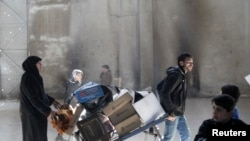 Sirijci kod Karaj al Hajeza, prelaza koji razdvaja deo Alepa pod kontrolom pobunjenika od područja koje kontroliše sirijska vlada, 4. februara 2014.