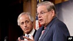 美国参议院外交委员会主席梅嫩德斯与(右)3月27日在国会山举行的记者会上