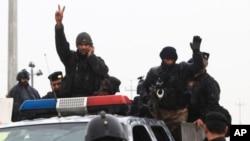"""Pasukan keamanan Irak menunjukkan tanda """"V"""" (kemenangan) setelah bertempur melawan militan pro al-Qaida di provinsi Anbar (5/1)."""