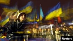 支持與歐洲融合的抗議者12月12日在基輔的獨立廣場揮舞旗幟