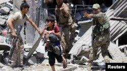 지난 7일 이라크 모술 서부 지역을 정부군이 순찰하는 가운데, 한 소년이 대피하고 있다.
