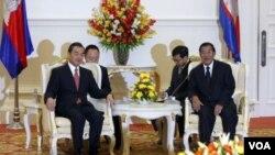 ລັດຖະມົນຕີຕ່າງປະເທດຈີນ ທ່ານ Wang Yi (ຊ້າຍ) ແລະ ນາຍົກລັດຖະມົນຕີກຳປູເຈຍ ທ່ານ Hun Sen ທີ່ກຸງພະນົມເປັນ.