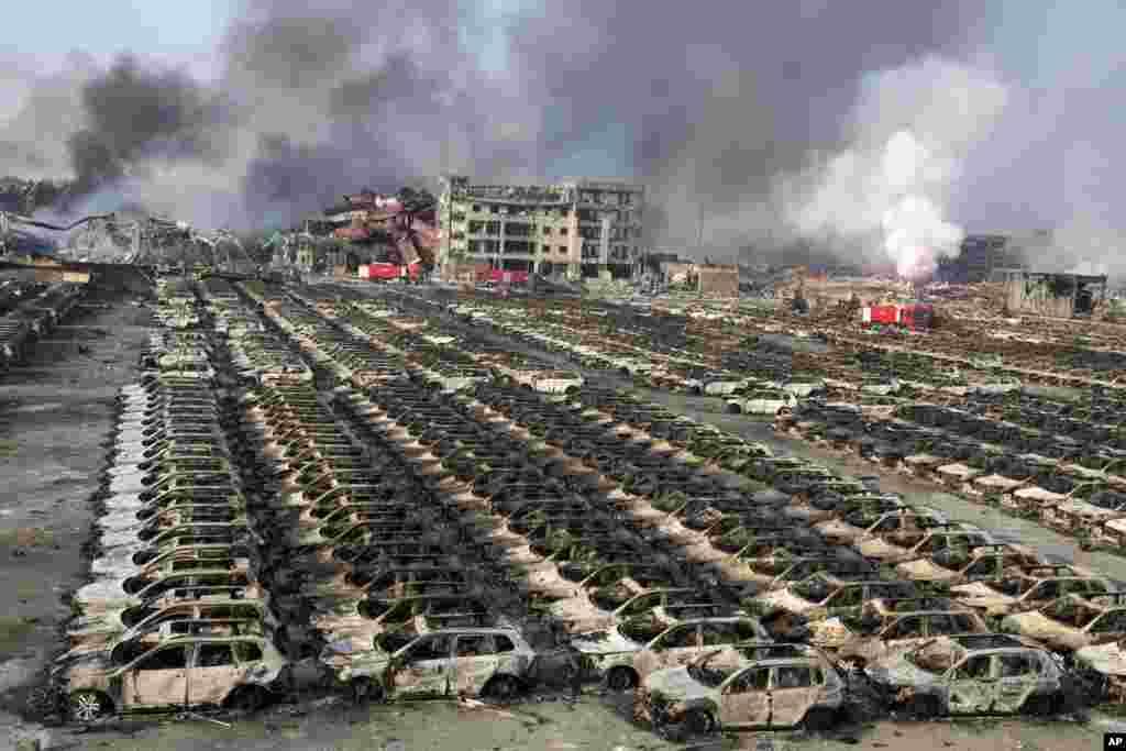 Asap membumbung dari lokasi ledakan yang menghanguskan mobil-mobil baru di lapangan parkir di sebuah gudang di timur laut kota Tianjin, China. Ledakan besar di gudang tersebut menghasilkan bola api yang menerangi kota tersebut hingga tampak seperti siang hari, menurut pejabat setempat dan saksi mata.