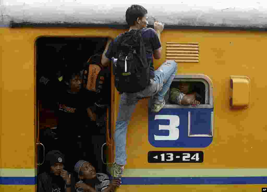 A passenger struggles for some space on an overcrowded train heading for East Java at Senen train station in Jakarta, Indonesia, September 2009 (AP)
