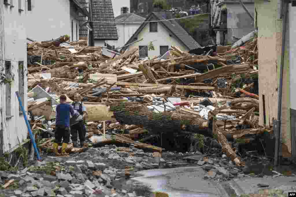 Two men remove debris of houses destroyed by the floods in Schuld near Bad Neuenahr, western Germany. Heavy flooding turned streams and streets into raging torrents, sweeping away cars and causing some buildings to collapse.