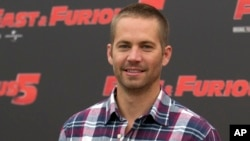 "FILE - In this April 29, 2011 file photo, actor Paul Walker poses during the photo call of the movie ""Fast and Furious 5,"" in Rome."