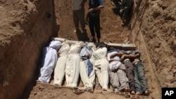 Foto tertanggal 21/8/2013 ini memperlihatkan jenasah yang dikubur secara masal di pinggiran Damascus akibat serangan senjata kimia yang disinyalir dilakukan oleh pemerintah Suriah kepada warganya.