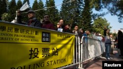 FILE - People line-up in front of polling station to vote during a civil referendum held by the Occupy Central organizers in Hong Kong January 1, 2014.