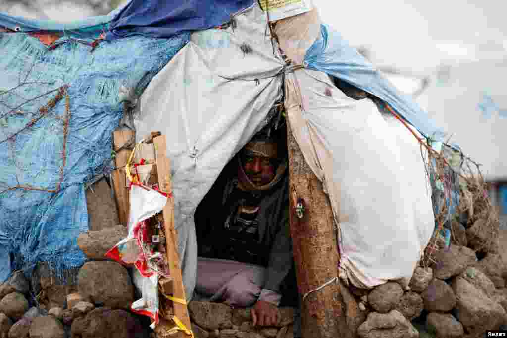 A man sits in his hut at a camp for internally displaced people near Sana'a, Yemen.