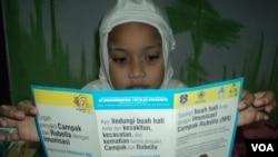 Seorang siswa SD membaca selebaran dari sekolah terkait imunisasi MR-Campak dan Rubella (Foto: VOA/Yudha).