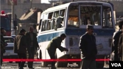 Warga setempat mengerumuni bus mini yang rusak akibat serangan bom bunuh diri, Rabu, 12 Januari 2011.