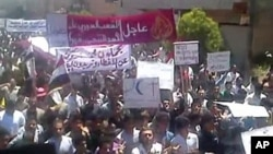An image grab taken from YouTube shows Syrian anti-regime protesters marching during a rally in the northeastern city of Kafr Nabl, June 3, 2011