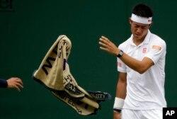 Kei Nishikori melempar handuknya dalam laga tunggal putera melawan petenis Italia,Marco Cecchinato, pada pembukaan turnamen Wimbledon di London, 3 Juli 2017.