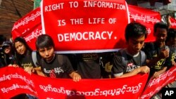 Burmese journalists hold banners as they protest for press freedom outside office of the Daily Eleven newspaper in Rangoon, Jan. 7, 2014.