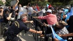 Cảnh sát chống bạo động sử dụng bình xịt hơi cay để đẩy lùi một nhóm biểu tình Uighur bên ngoài Đại sứ quán Trung Quốc tại Thổ Nhĩ Kỳ. (AP Photo/Burhan Ozbilici)