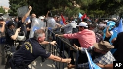 FILE - Riot police use pepper spray to push back a group of Uighur protesters who try to break through a barricade outside the Chinese Embassy in Ankara, Turkey, June 9. 2015.