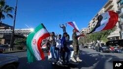 Piştgirên rejîma Sûrî alayên Îranî û Rûsî bilind dikin