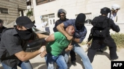 Israeli riot and undercover policemen arrest a Palestinian protester during clashes in the east Jerusalem Arab neighborhood of Issawiya, May 15, 2012.