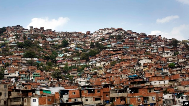 FILE - A hill covered with low-income houses is seen in Petare district, Caracas, March 6, 2014.