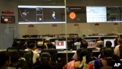 Para ilmuwan Organisasi Riset Antariksa India (ISRO) menonton grafik yang menjelaskan Misi Pengorbit Mars di kompleks kantor mereka di Bangalore, India (24/9). (AP/Aijaz Rahi)