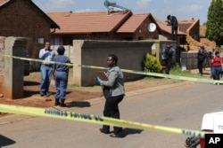 Police, forensic investigators and press work outside the home of actress and singer, Kelly Khumalo, in Vosloorus, east of Johannesburg, South Africa, Oct. 27, 2014.