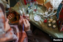 Palestinian Hanan Al-Madhoon paints a glass as she makes decorations for sale ahead of the holy fasting month of Ramadan, at Beach refugee camp in Gaza City April 6, 2021. Picture taken April 6, 2021. REUTERS/Suhaib Salem