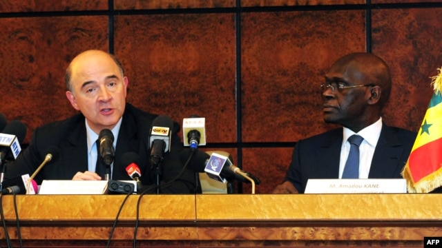 French Economy Minister Pierre Moscovici (L) speaks beside his Senegalese counterpart Amadou Kane, Apr. 8, 2013, during a press conference in Dakar, following a meeting of ministers of the member countries of the West African franc zone.